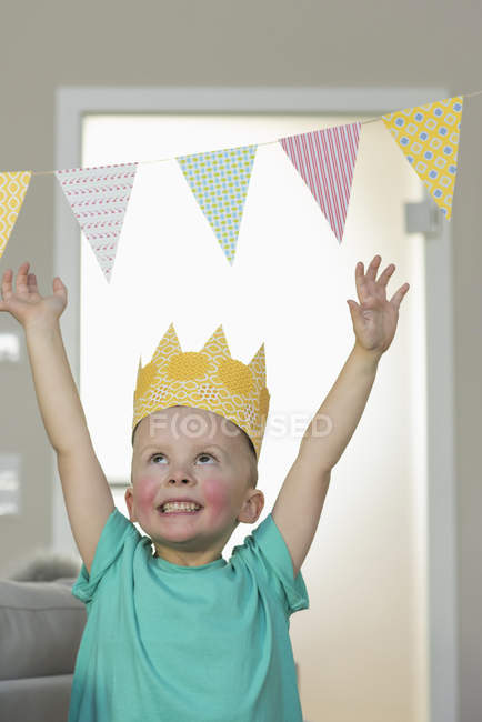 Happy boy wearing paper crown at home — Stock Photo