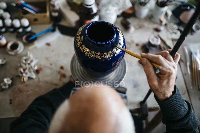Senior man decorating ceramic vase in his spare time — Stock Photo