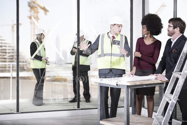 Architect wearing safety vest talking to man and woman — Stock Photo
