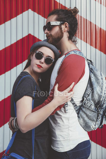 Young couple wearing sunglasses embracing on the street — Stock Photo