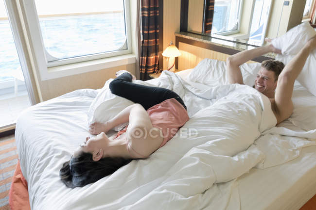 Young couple on cruise lying in bed having a pillow fight — Stock Photo