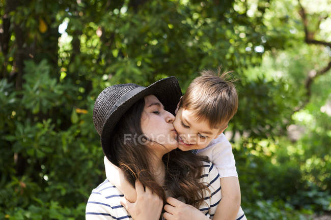 Mother kissing son outdoors — Stock Photo
