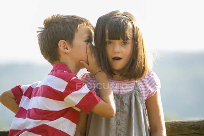 Little boy whispering secret in astonished girl ear — Stock Photo