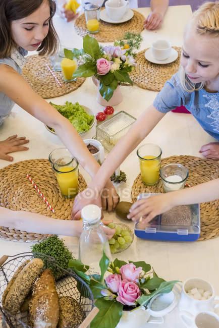 Niñas alcanzan para el alimento en la mesa puesto - foto de stock