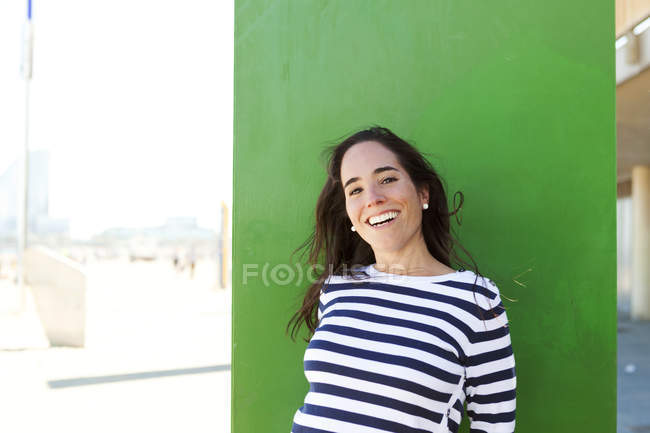 Portrait of happy woman at green wall — Stock Photo
