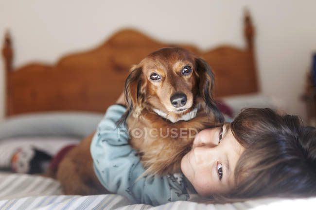 Smiling little boy lying on bed with long-haired Dachshund — Stock Photo