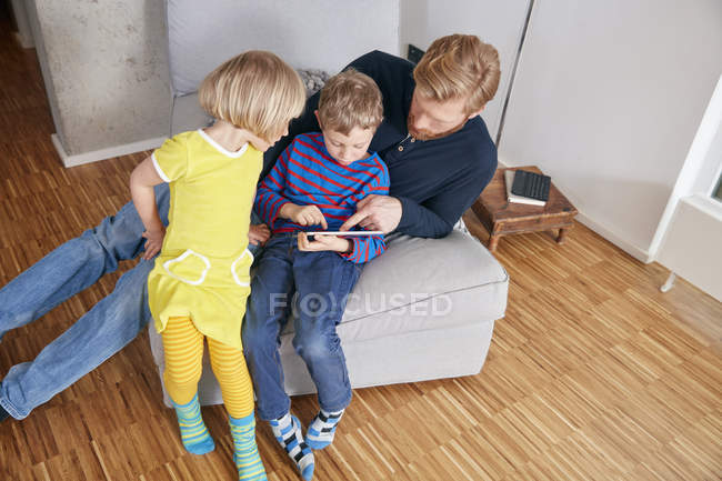 Отец и двое детей с помощью цифрового планшета — стоковое фото