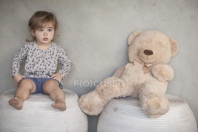Серйозні дитини дівчина і плюшевого ведмедика, сидячи на стільці — стокове фото