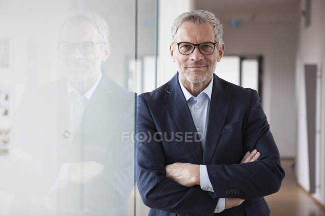 Successful businessman standing in his office with arms crossed — Stock Photo