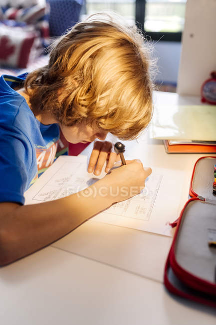 Portrait of pensive boy doing homework at home — Stock Photo