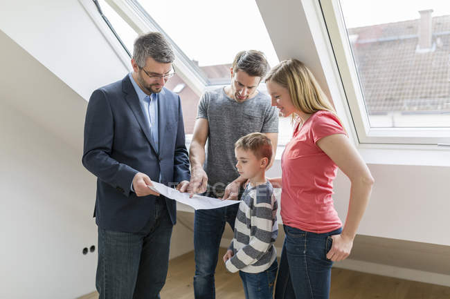 Estate agent explaining family construction plan of a penthouse — Stock Photo