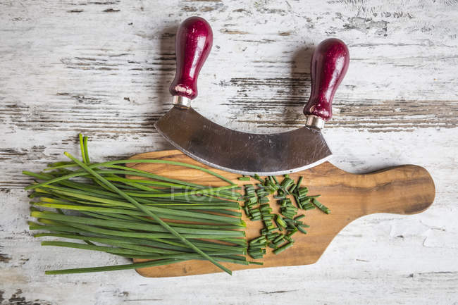 Chives, mezzaluna and wooden board on wood — Stock Photo
