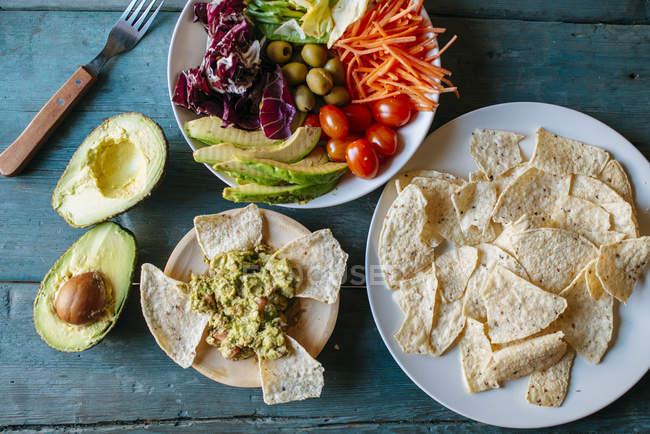 Vue de dessus de l'avocat, guacamole, nachos et salade mixte — Photo de stock