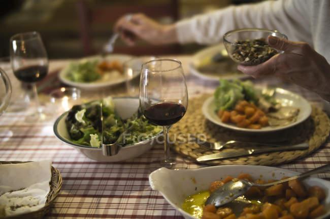 Vista recortada de la mesa entregada servida para la cena con vino tinto - foto de stock