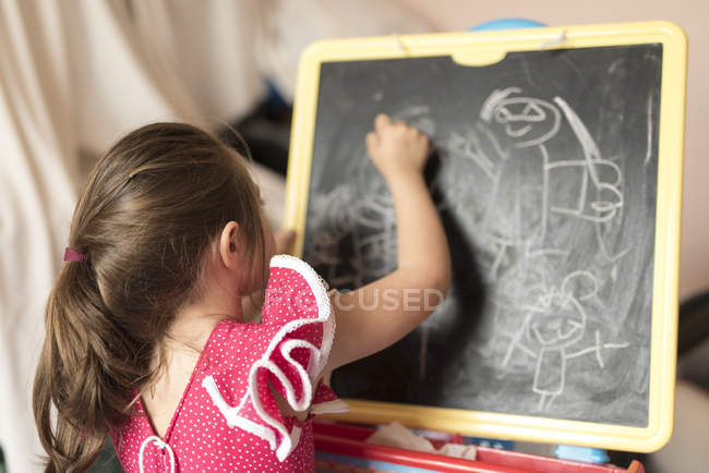 Маленька дівчинка малюнок на борту крейда — стокове фото