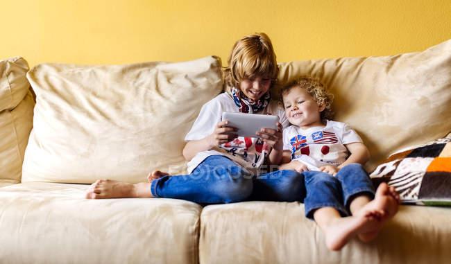 Zwei lächelnde Jungen auf der Couch mit digitalem Tablet — Stockfoto