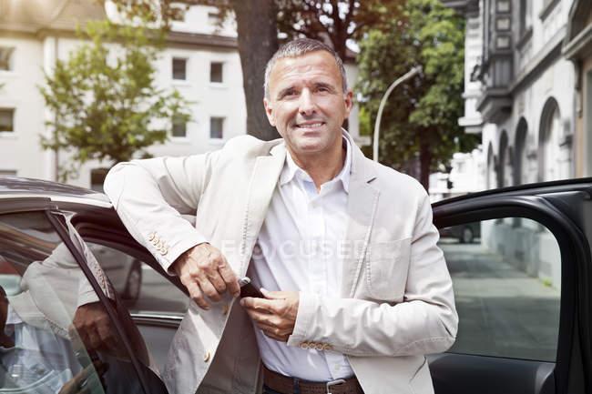 Ritratto dell'uomo sorridente che si appoggia alla portiera della macchina aperta con le chiavi della macchina — Foto stock