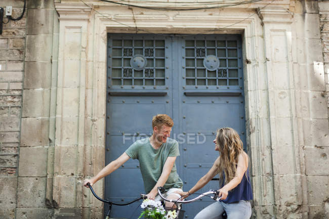 Laughing couple with bicycles outdoors — Stock Photo