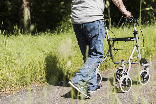 Back view of senior man strolling with wheeled walker in nature — Stock Photo