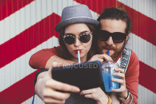 Young couple with soft drinks taking selfie with smartphone — Stock Photo