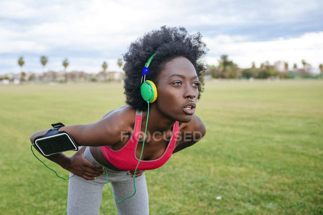 Female athlete listening music with headphones while warming up — Stock Photo