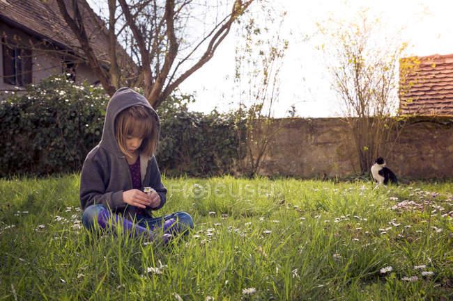Mädchen mit Kapuzenjacke sitzt auf Wiese — Stockfoto