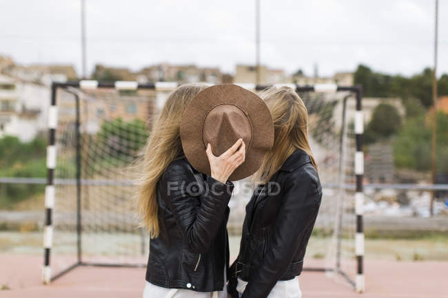 Two women standing on sports field covered with hat — Stock Photo