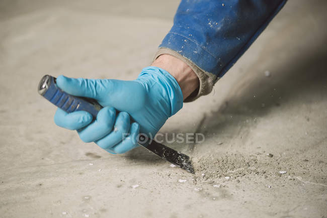 Bricklayer removing irregularities on floor screed with spatula — Stock Photo