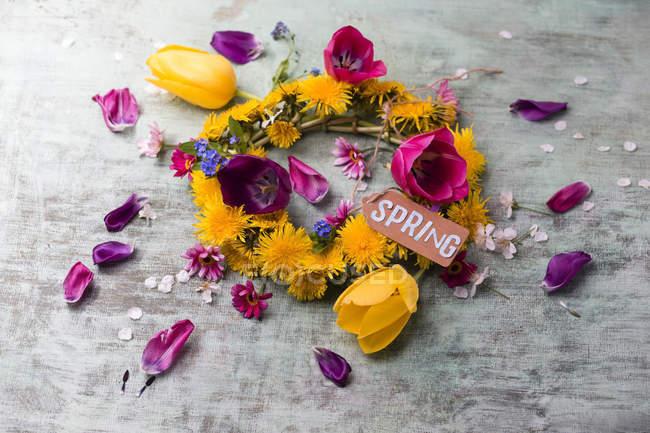 Grinalda de dente-de-leão, tulipas e margueritas — Fotografia de Stock