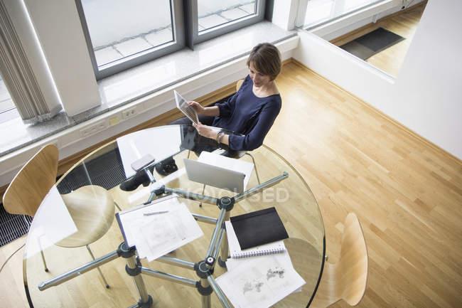 Femme d'affaires avec tablette numérique et ordinateur portable à la table de bureau — Photo de stock