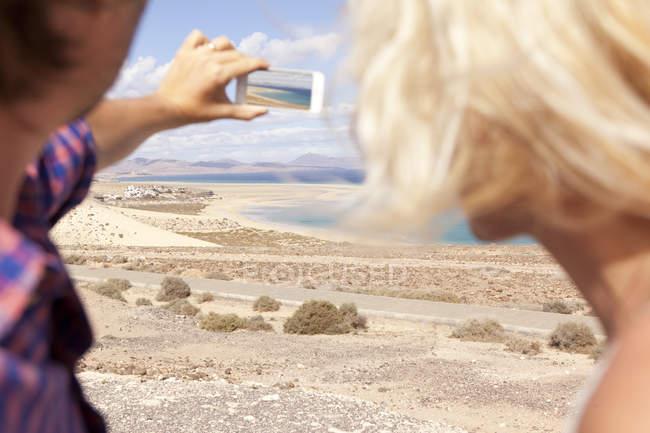 Spain, Fuerteventura, Jandia, couple taking photo at the coast — стоковое фото