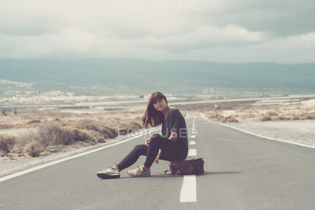 Young woman with suitcase sitting on the road — Stock Photo
