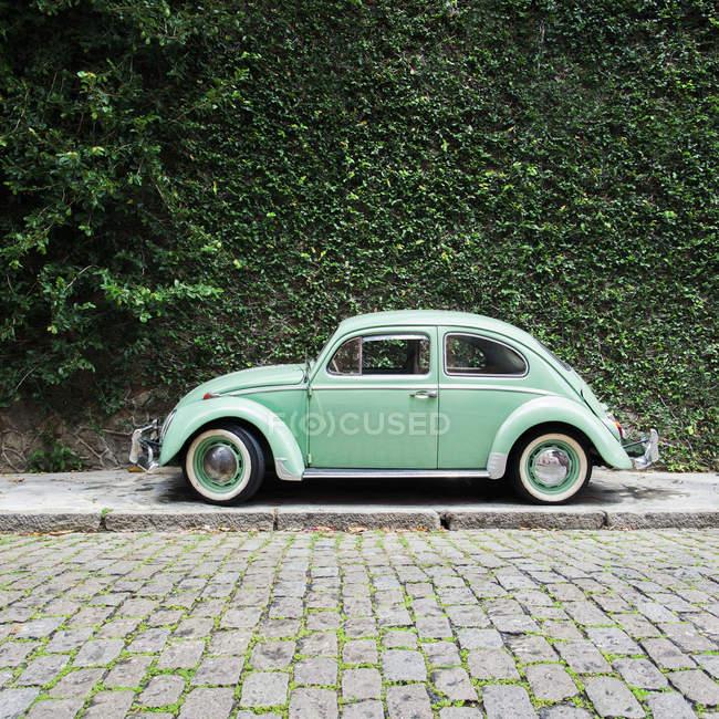 Brasil, Río de Janeiro - Coche verde vintage en frente de la pared verde cubierto - foto de stock