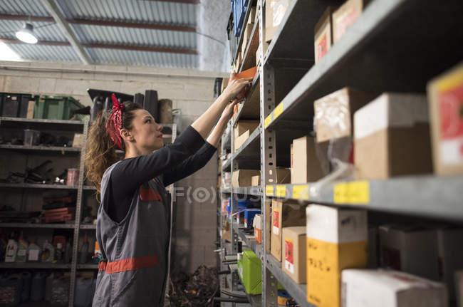 Femme dans l'entrepôt, elle examine les boîtes. — Photo de stock