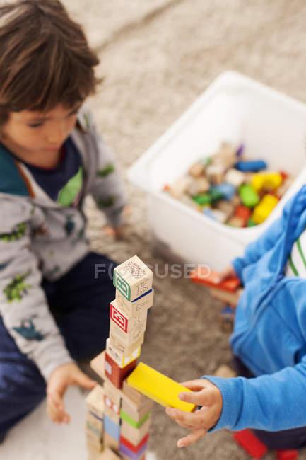 Zwei kleine Jungen bauen einen Turm mit Bauklötzen — Stockfoto