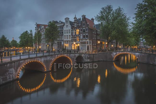 Países Bajos, Condado de Holanda, Amsterdam, Canal del Emperador y Canal de Leidse por la noche, Puente - foto de stock