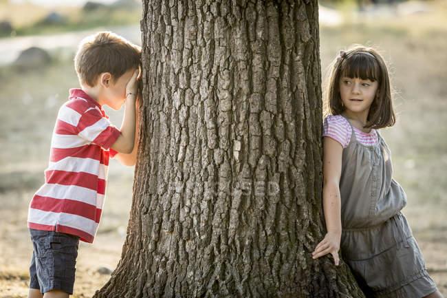 Ragazzino e ragazza che gioca a nascondino in natura — Foto stock