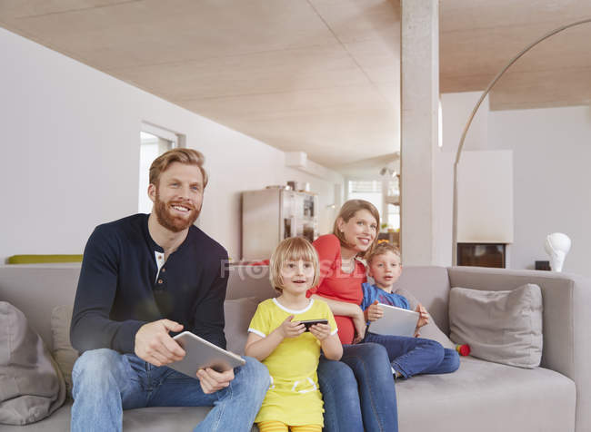 Family holding mobile devices on couch at home — Stock Photo