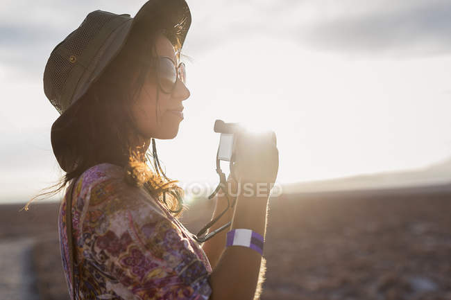 Woman with camera in the desert — Stock Photo