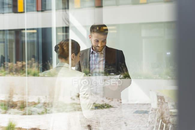 Двома колегами, обговорювати папір у вікно в офісі — стокове фото