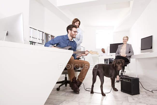 Quatre collègues font une pause dans le bureau pour regarder un chien — Photo de stock