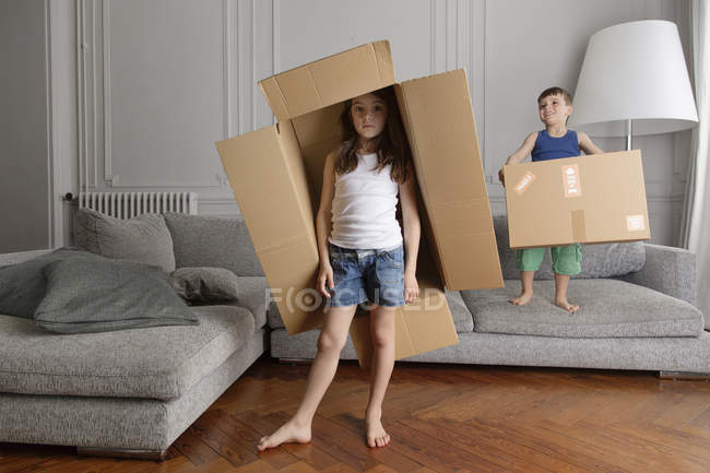Girl and brother playing with cardboard boxes at home — Stock Photo