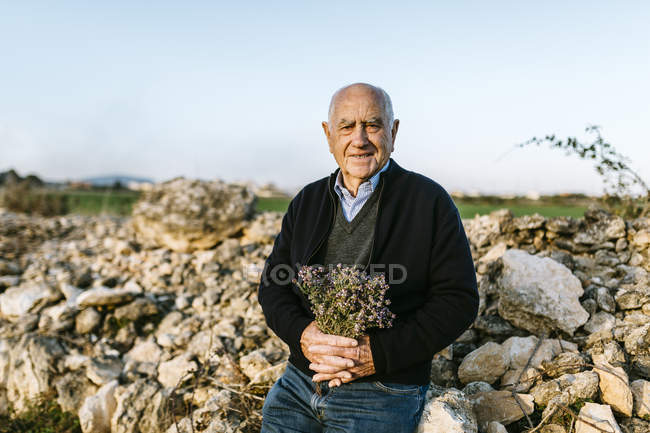 Senior man with bouquet of flowers — Stock Photo
