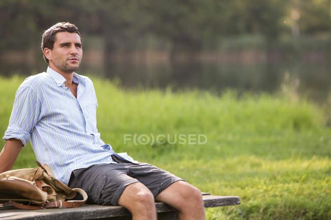Ritratto di giovane seduto su un molo al lago — Foto stock