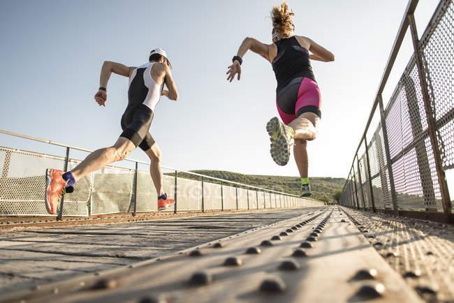 Два молодих спортсменів працює на мосту — стокове фото