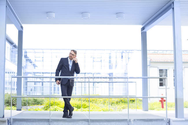 Businessman standing next to office building — Stock Photo