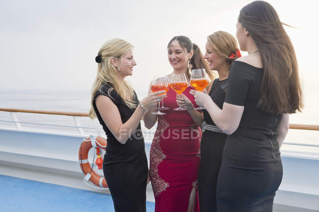 Four women toasting with aperitive on a cruise liner — Stock Photo