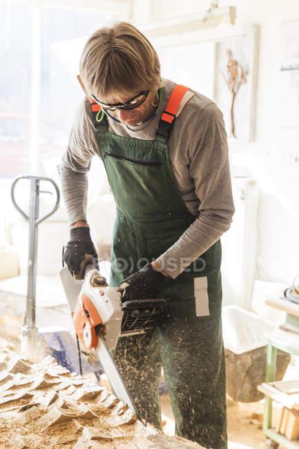 Holzschnitzer in der Werkstatt bearbeitet Holz mit der Kettensäge — Stockfoto