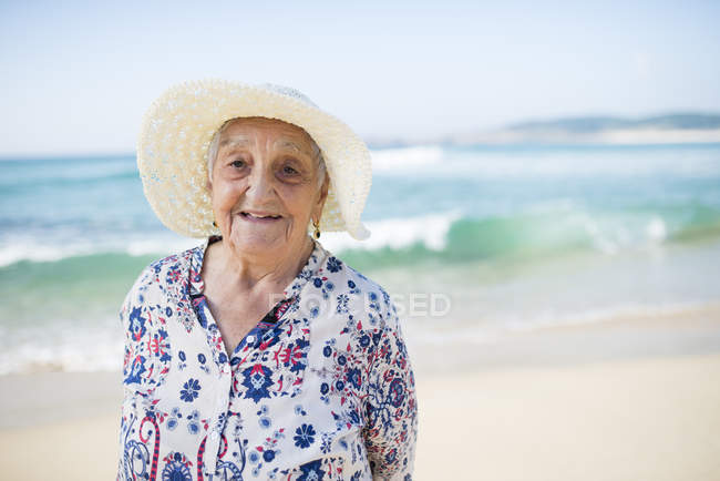 Portrait of smiling senior woman standing on the beach — Stock Photo