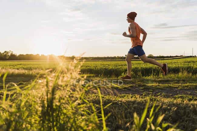 Jeune homme jogging, contre le soleil — Photo de stock